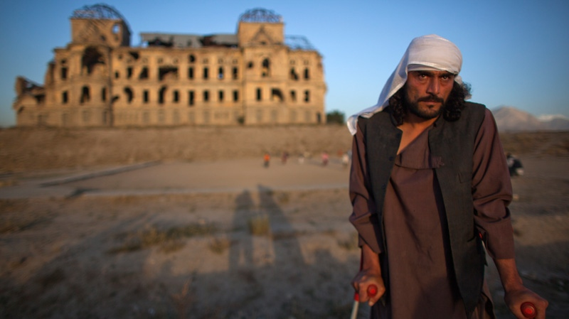 Wahidullah, 32, whose spine was pierced by a bullet during the civil war that left him crippled, poses for a photograph in front of Darul Aman Palace which was damaged during the civil war in Kabul, Afghanistan on Thursday, Oct. 4, 2012. (AP /Dusan Vranic)