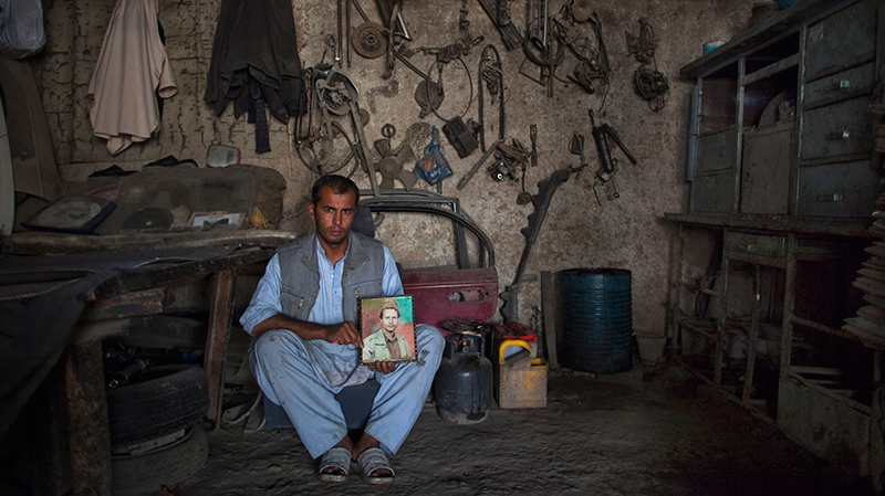 Shah Ker, 29, a car mechanic, poses in the shop he inherited from his father Ramdil Shah who was killed during the Afghan civil war in 1993 in Kabul, Afghanistan on Saturday, Oct. 6, 2012. (AP /Dusan Vranic)