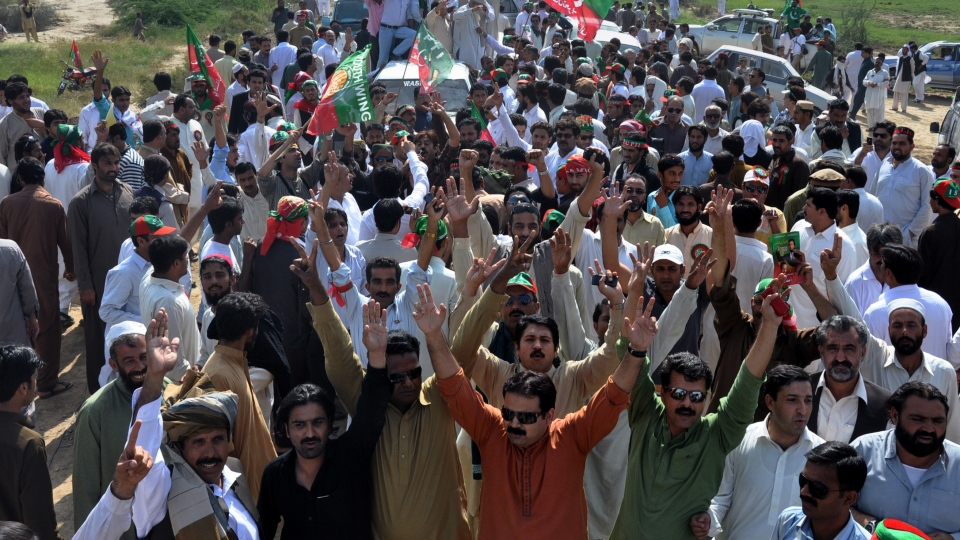 Supporters of Pakistan's cricket star turned politician Imran Khan's party, not pictured, raise their hands during a peace march on the outskirts of Tank, Pakistan on Sunday, Oct. 7, 2012.  (AP /Mohammad Hussain)