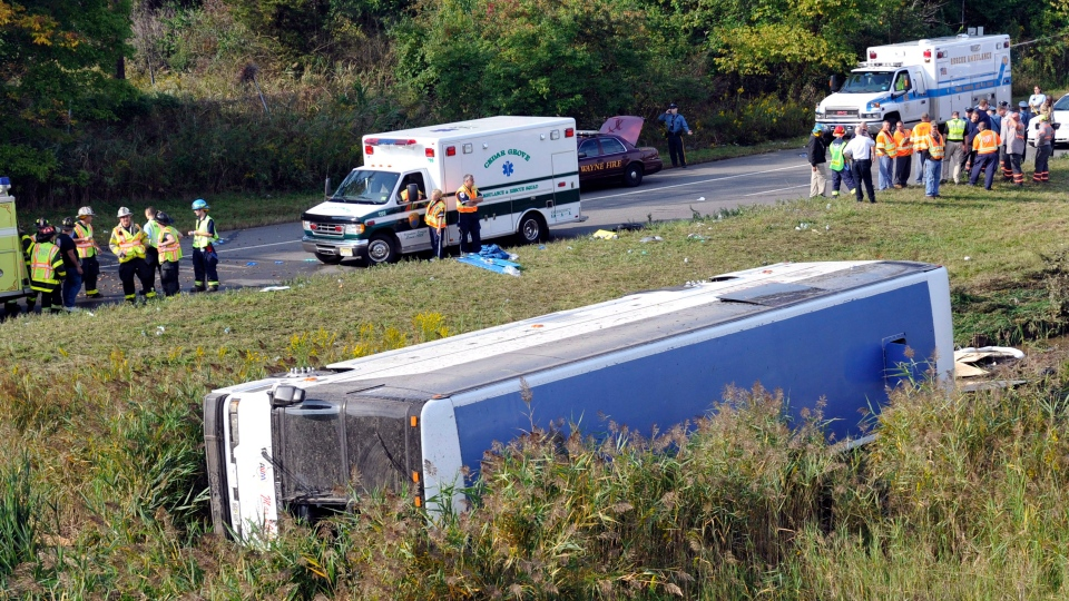 Rescue workers stand by after a bus overturned in a ditch at an exit ramp off Route 80 in Wayne, N.J. Saturday, Oct. 6, 2012. (AP / Bill Kostroun)