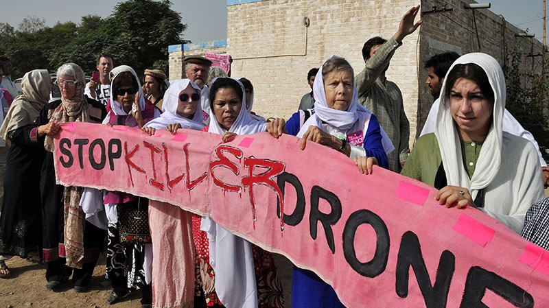 American citizens, hold a banner during a peace march organized by Pakistan's cricket star turned politician Imran Khan's party, not pictured, in Tank, Pakistan, Sunday, Oct. 7, 2012. (AP / Mohammad Hussain)