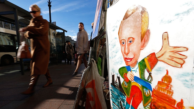 People walk past a cartoon depicting Russia's President Vladimir Putin displayed by a street artist in St.Petersburg, Russia, Sunday, Oct. 7, 2012.  (AP Photo/Dmitry Lovetsky)