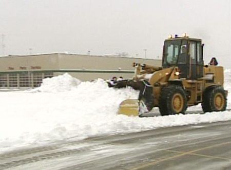 Crews work to clear snow from covered roads in Toronto on Wednesday, Feb. 6, 2008.