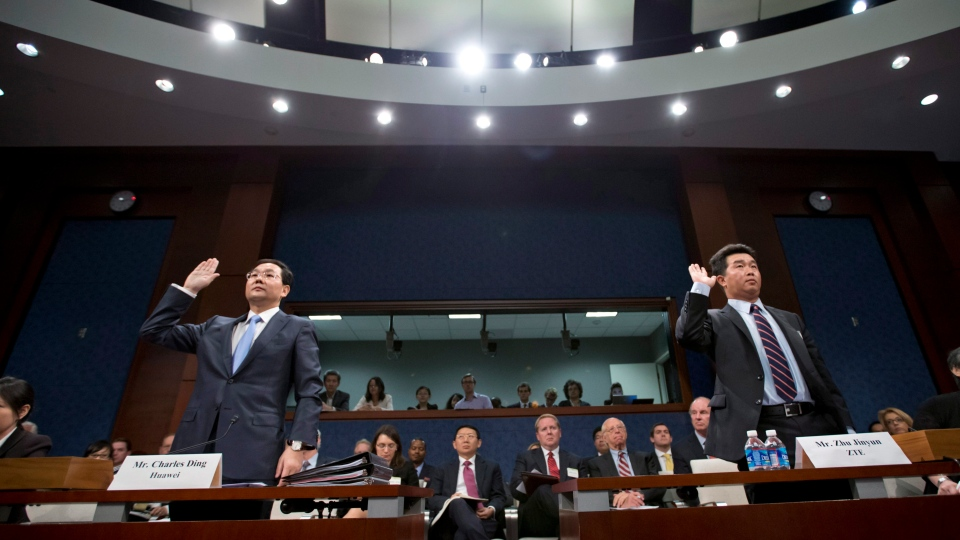 Executives of two major Chinese technology companies, Charles Ding, Huawei Technologies Ltd senior vice president for the U.S., left, and Zhu Jinyun, ZTE Corporation senior vice president for North America and Europe, are sworn in on Capitol Hill in Washington, Thursday, Sept. 13, 2012. (AP / J. Scott Applewhite)