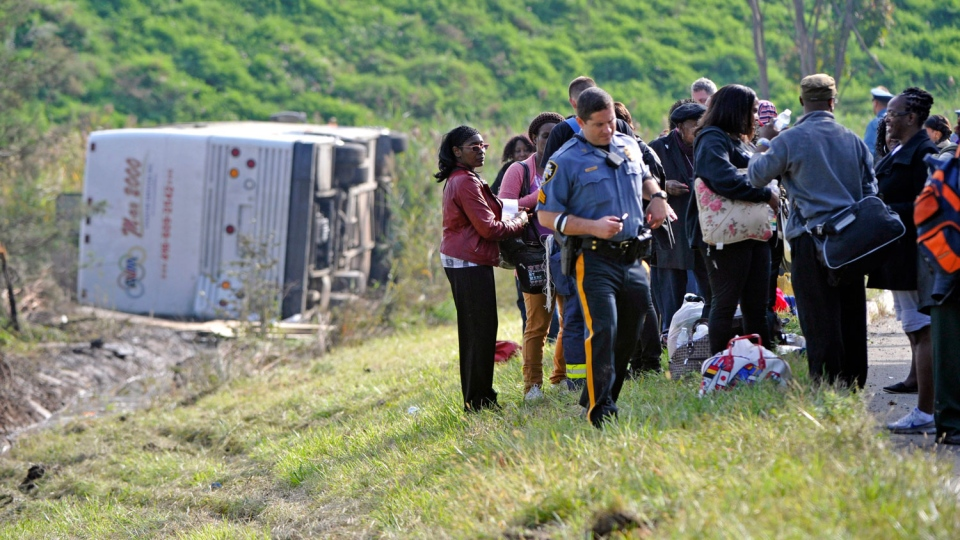 Passengers look on after their bus overturned in a ditch at an exit ramp off Route 80 in Wayne, N.J. Saturday, Oct. 6, 2012. (AP / Bill Kostroun)