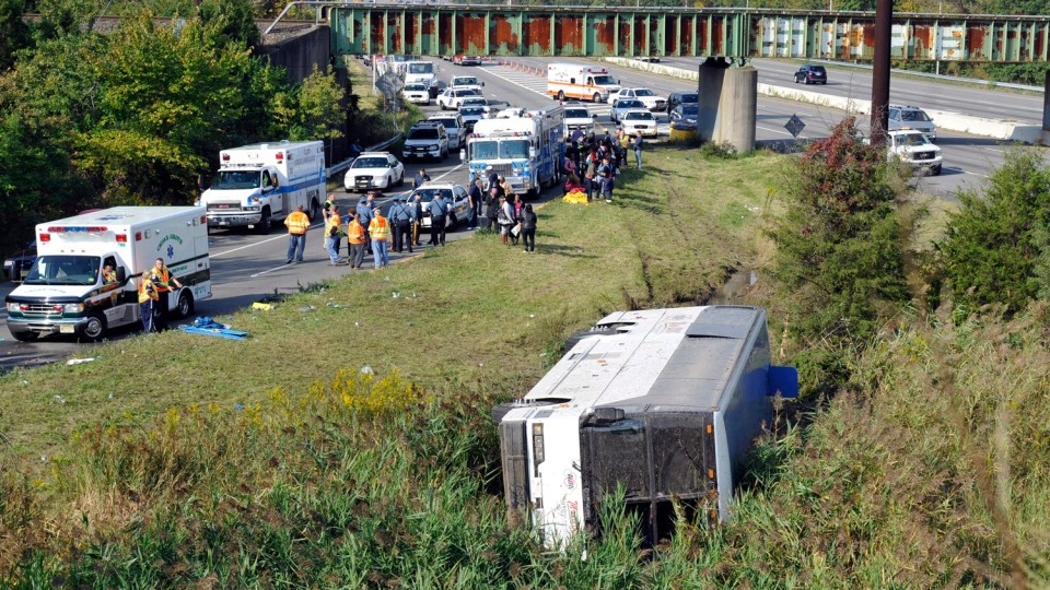 Rescue workers and passengers stand by after a bus overturned in a ditch at an exit ramp off Route 80 in Wayne, N.J. Saturday, Oct. 6, 2012.  (AP / Bill Kostroun)