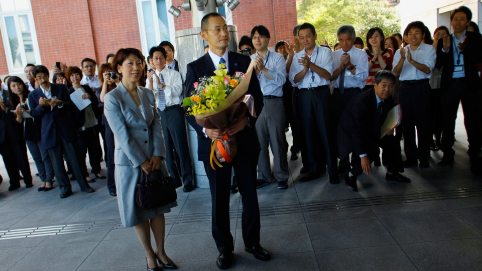 Nobel prize laureate in medicine Shinya Yamanaka of Japan, 50, foreground right, and his wife Chika are greeted by school employees at Kyoto University while arriving for a press conference in Kyoto, western Japan, Tuesday, Oct. 9, 2012. (AP / Junji Kurokawa)