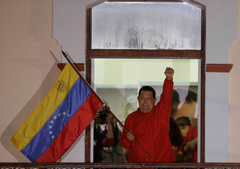 Venezuela's President Hugo Chavez waves a Venezuelan flag as he greets supporters at the Miraflores presidential palace balcony in Caracas, Venezuela, Sunday, Oct. 7, 2012. (AP / Fernando Llano)