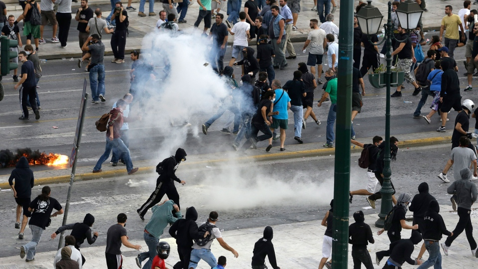 Protestors run away from tear gas during clashes in front of the parliament in Athens on Tuesday Oct. 9, 2012. (AP / Dimitri Messinis)