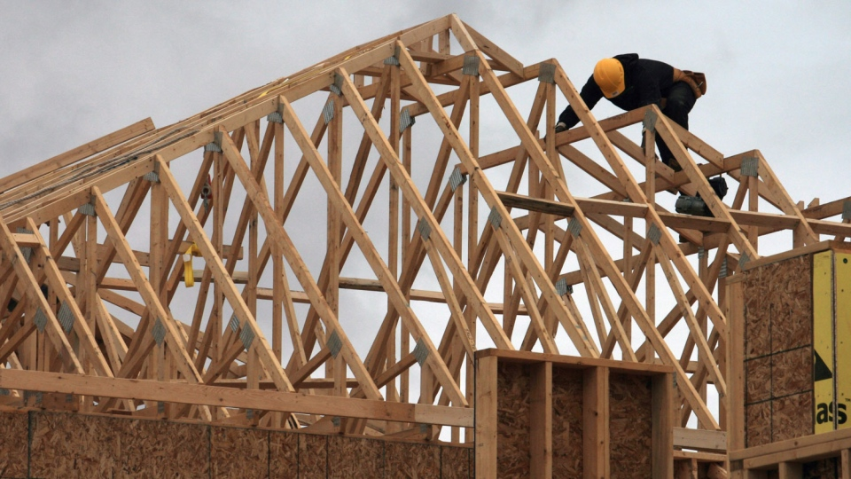 A construction worker works on a house in a new housing development in Oakville, Ont., north of Dundas Street, Friday, April 29. 2011. (Richard Buchan / THE CANADIAN PRESS)