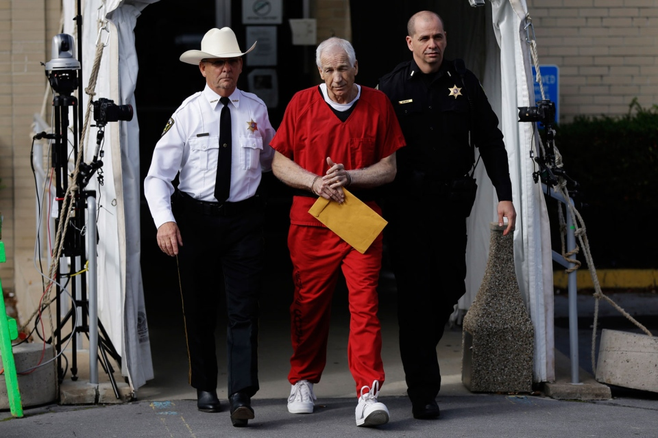 Former Penn State University assistant football coach Jerry Sandusky, center, is taken from the Centre County Courthouse by Centre County Sheriff Denny Nau, left, and a deputy, after being sentenced in Bellefonte, Pa., Tuesday, Oct. 9, 2012. (AP / Matt Rourke)