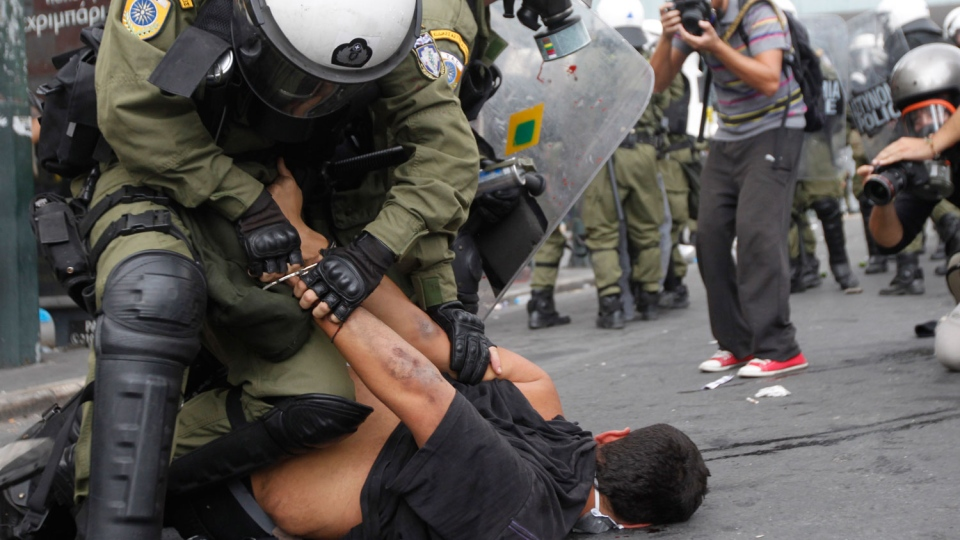 Riot police arrest a demonstrator during clashes in front of the parliament in Athens, Tuesday, Oct. 9, 2012. (AP / Nikolas Giakoumidis)