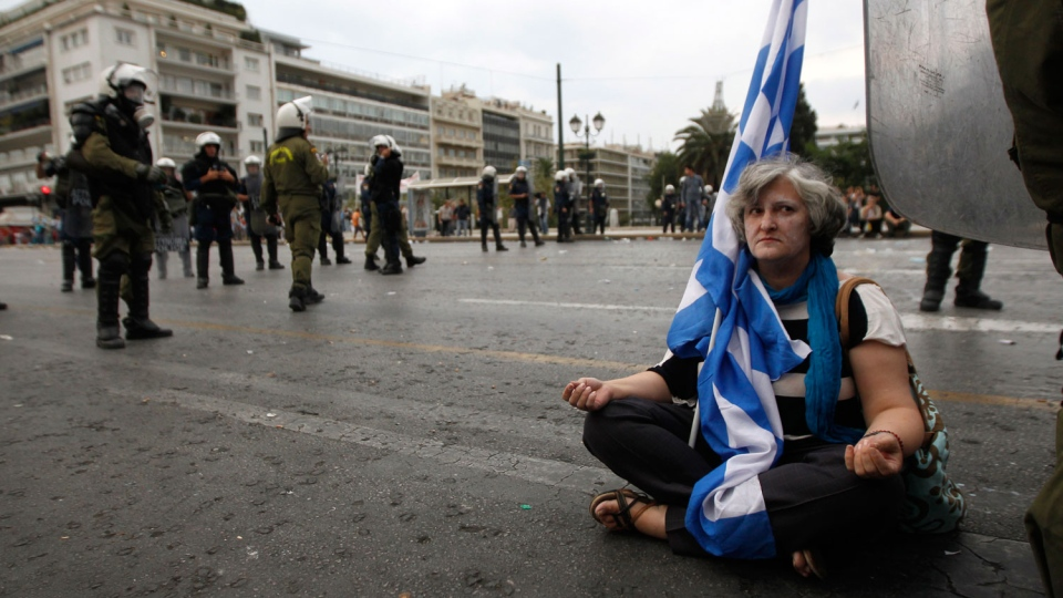 A peaceful demonstrator sits on the ground surrounded by riot police in front of the parliament, at the end of a demo in Athens on Tuesday Oct. 9, 2012. (AP / Nikolas Giakoumidis)