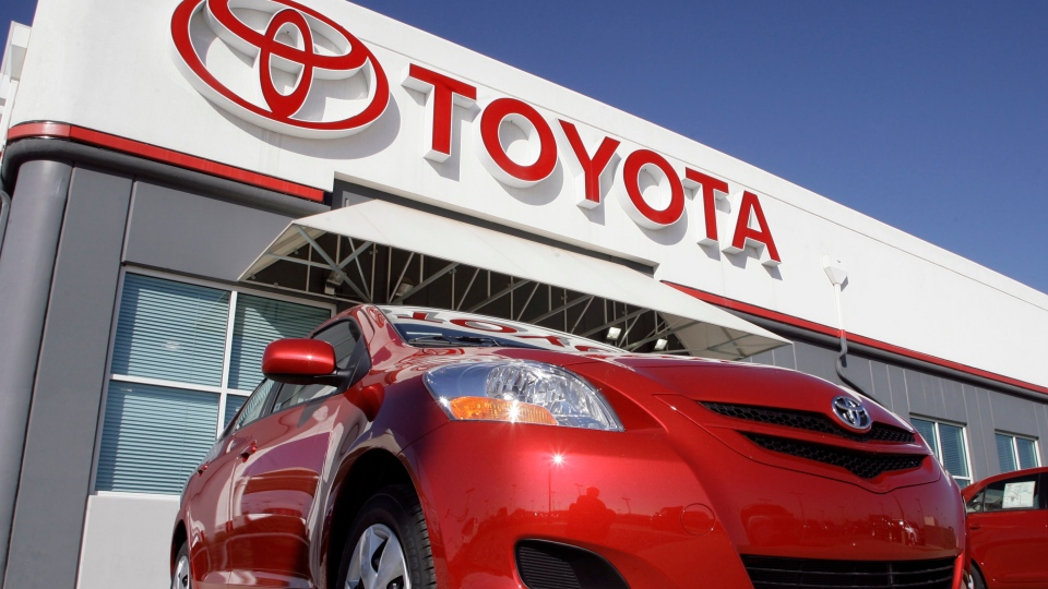The Toyota sign hangs over a 2007 Yaris sedan on sale on the lot of a Toyota dealership in the southeast Denver suburb of Centennial, Colo., Oct. 22, 2006. (AP / David Zalubowski)