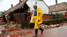 A villager walks in front of houses destroyed by a flood of toxic mud in Kolontar, Hungary, Wednesday, Oct. 6, 2010.(AP / Bela Szandelszky)