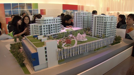 Prospective buyers look at a model of Vancouver's Olympic Village on Oct. 6, 2010. (CTV)