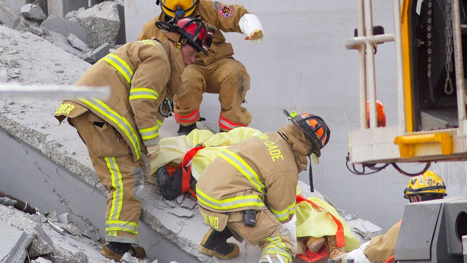 Fire Rescue officials work to remove a victim from the collapsed parking garage at the Miami Dade College West campus in Doral, Fla. Tuesday, Oct. 10, 2012. (AP / J Pat Carter)