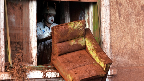 A worker, wearing a protective gear,discards furniture from a house damaged by flooding toxic mud in the village of Kolontar, Hungary, Thursday, Oct. 7, 2010. (AP / Bela Szandelszky)
