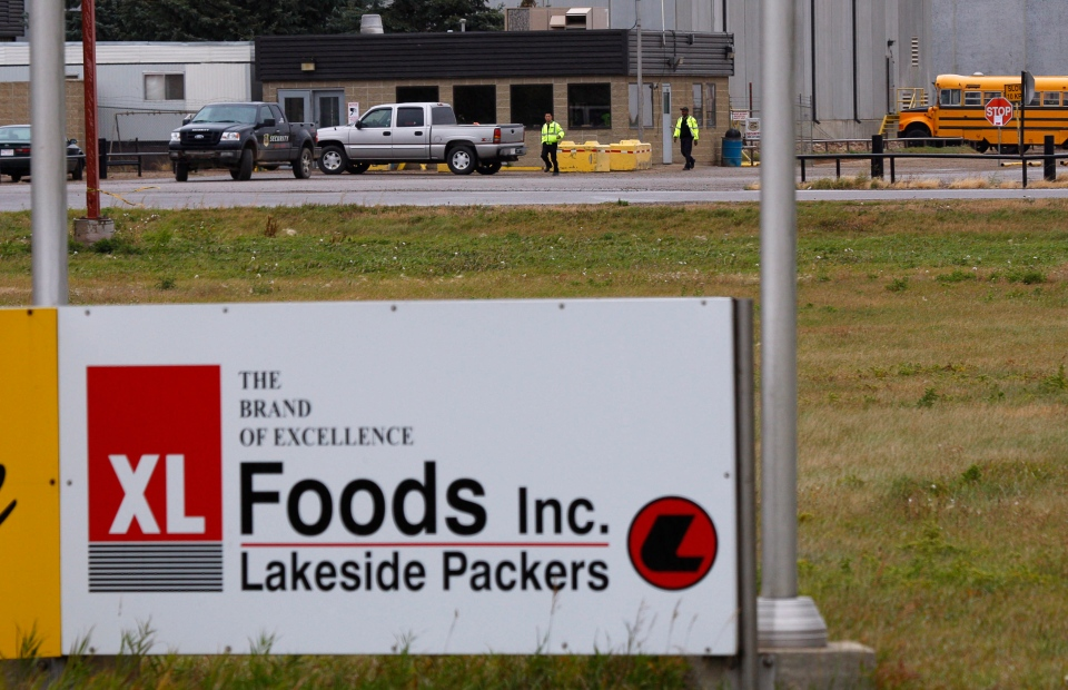 Security personnel patrol the XL Foods cattle processing plant in Brooks, Alta., Wednesday, Oct. 10, 2012. (Jeff McIntosh / THE CANADIAN PRESS)