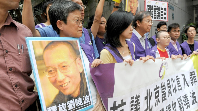 Pro-democracy protesters hold the picture of Chinese dissident Liu Xiaobo with Chinese words 'Release Liu Xiaobo' during a demonstration outside the China Liaison Office in Hong Kong, Friday, Oct. 8, 2010. (AP / Apple Daily)