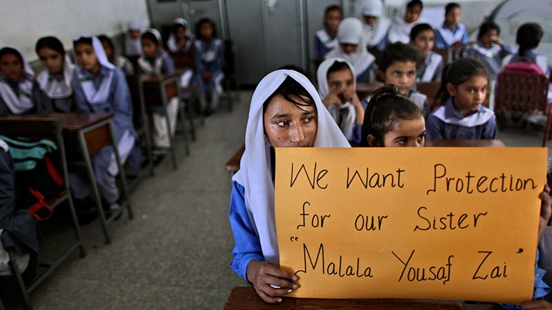Pakistani girls display a poster