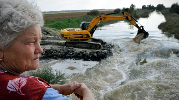 Eszter Horvath a resident of Mezolak, Hungary, looks on as an excavator pours plaster into the river Marcal to neutralize the polluting toxic sludge near to her village, Friday Oct. 8, 2010. (AP / Bela Szandelszky)