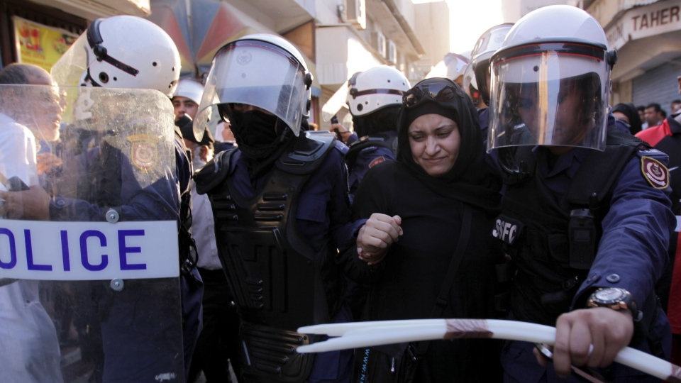 Riot policewomen arrest a Bahraini anti-government protester while dispersing a march through narrow market streets of the capital of Manama, Bahrain, on Friday, Oct. 12, 2012.  (AP / Hasan Jamali)