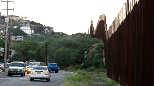 Vehicles drive along the border fence in Nogales, Mexico, Thursday, Aug. 9, 2012. (AP / Ross D. Franklin)