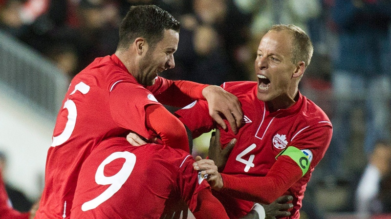 Canada's Tosaint Ricketts (9) celebrates with teammates Kevin McKenna (4) and David Edgar, left, after scoring against Cuba during the first half of a World Cup qualifying soccer match in Toronto on Friday, Oct. 12, 2012. (AP Photo/The Canadian Press, Nathan Denette)