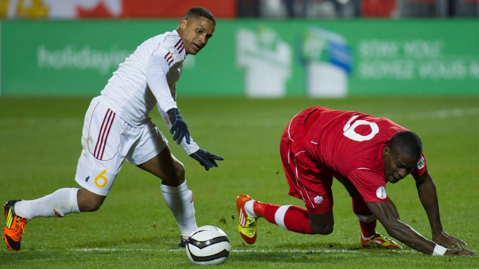 Cuba's defender Yoel Colome, left, trips up Canada's Tosaint Ricketts, right, during second half FIFA World Cup Qualifier soccer action in Toronto on Friday, Oct. 12, 2012.( THE CANADIAN PRESS/Nathan Denette)