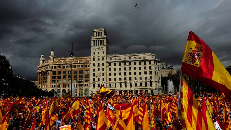 People opposed to the independence of the Catalonia region of Spain hold Catalan and Spanish flags during the holiday known as Dia de la Hispanidad, Spain's National Day in Barcelona, Spain, Friday, Oct. 12, 2012. (AP / Manu Fernandez)