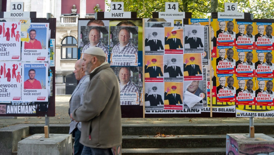 Two men walk by election campaign posters in Antwerp, Belgium, Monday, Oct. 8, 2012. (AP / Virginia Mayo)