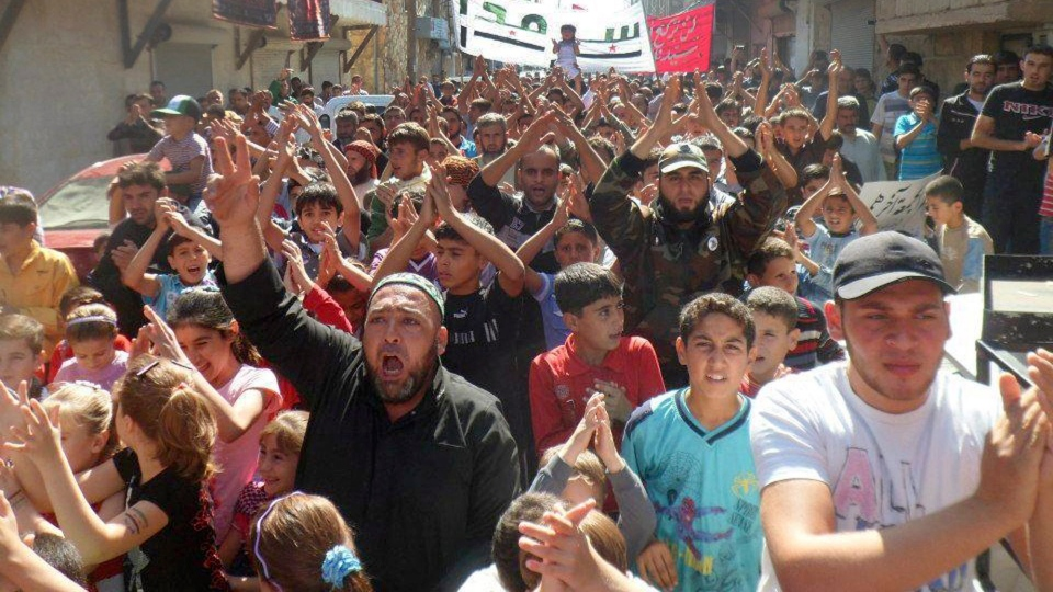 Anti-Syrian regime protesters raise their hands and shout slogans during a demonstration at Sarmada village, in Idlib province, northern Syria, on Friday Oct. 12, 2012. (AP / Edlib News Network ENN)