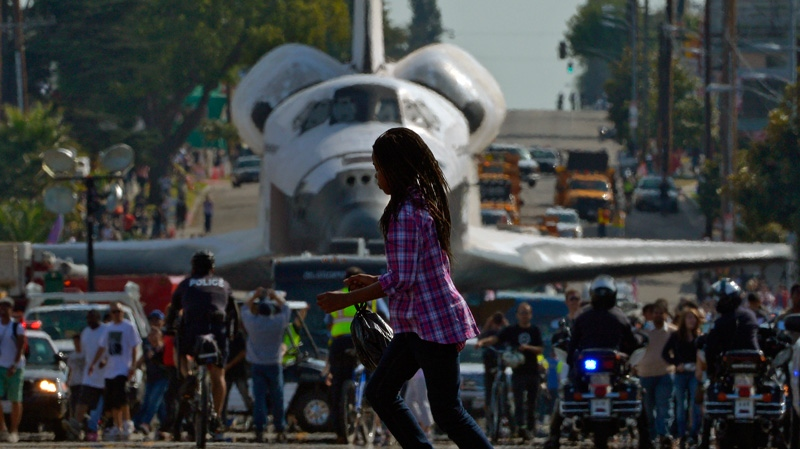 A young woman runs across the street in front of the space shuttle Endeavour as it is slowly moved down Crenshaw Blvd., Saturday, Oct.13, 2012, in Los Angeles. (AP Photo/Mark J. Terrill)
