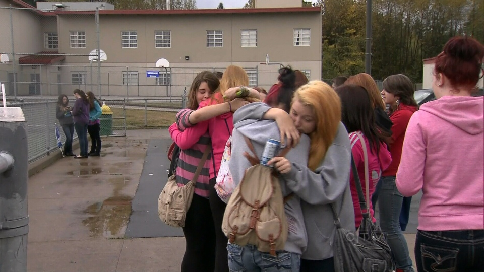 Former classmates of Amanda Todd console eachother at a football game in Maple Ridge, B.C. on Saturday, Oct. 13, 2012.