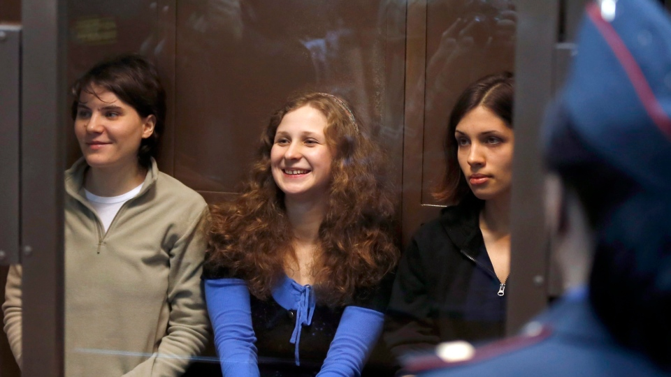 Feminist punk group Pussy Riot members, from left, Yekaterina Samutsevich, Maria Alekhina, and Nadezhda Tolokonnikova sit in a glass cage at a court room in Moscow on Wednesday. Oct. 10, 2012. (AP /Sergey Ponomarev)