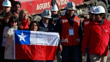 A relative of a trapped miner holds a Chilean flag as mining officials and people involved in the rescue effort of 33 trapped miners look on at the San Jose mine near Copiapo, Chile, Saturday, Oct. 9, 2010. (AP / Dario Lopez-Mills)