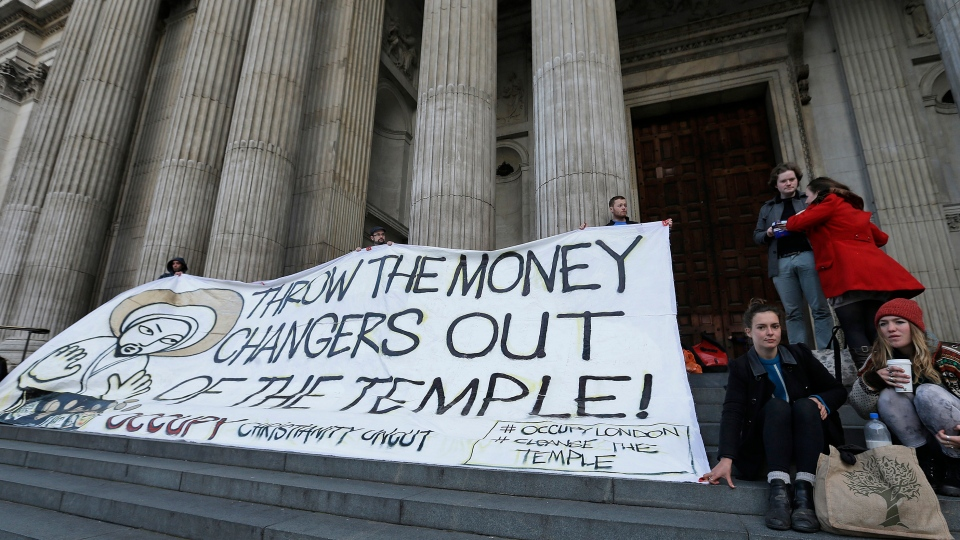 Activists of the Occupy movement hold a banner saying 'Throw the Money Makers out of the Temple' outside of St Paul's Cathedral in London Sunday, Oct. 14, 2012. (AP / Alastair Grant)