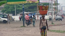 Woman walks with basket in Kinshasa