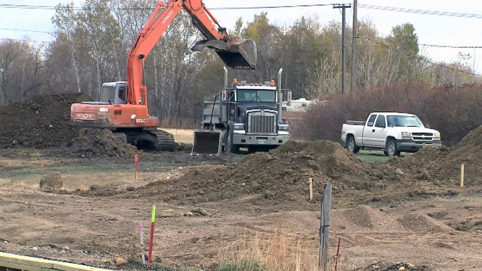 A construction crew works on a lot in Reston, Manitoba, Sunday, Oct. 14, 2012.