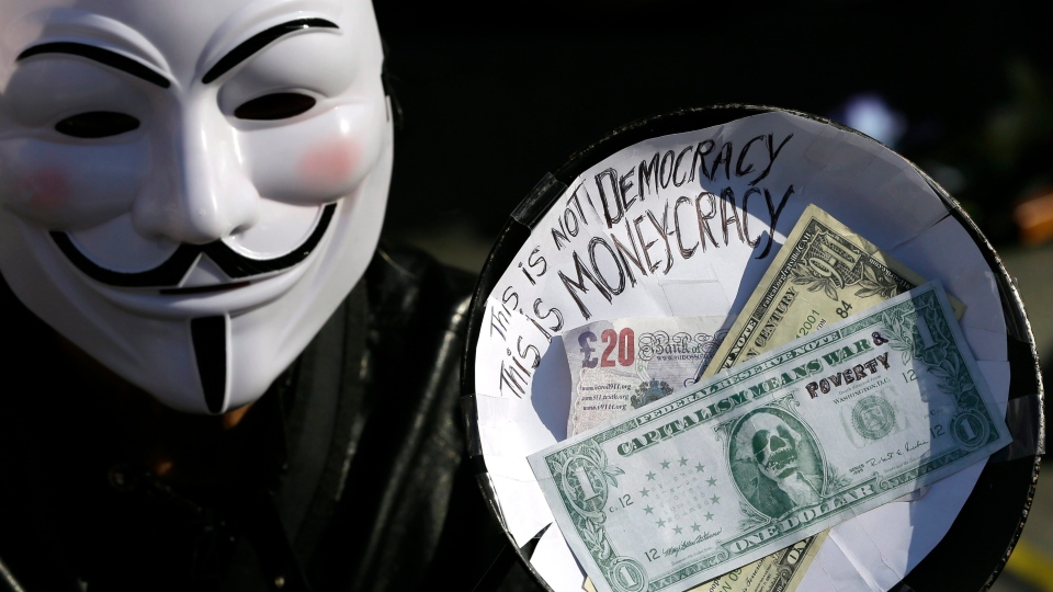 A demonstrator wearing a mask holds a decorated frying pan as people celebrate the anniversary of 'Occupy' outside St Paul's cathedral in London, Saturday, Oct. 13, 2012. (AP / Kirsty Wigglesworth)