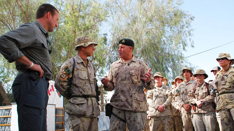 Defence Minister Peter MacKay, left, and Chief of Defence Staff Walter Natynczyk, centre, talk to Canadian soldiers in Kandahar, Afghanistan, Sunday, Oct. 10, 2010. (Jonathan Montpetit / THE CANADIAN PRESS)