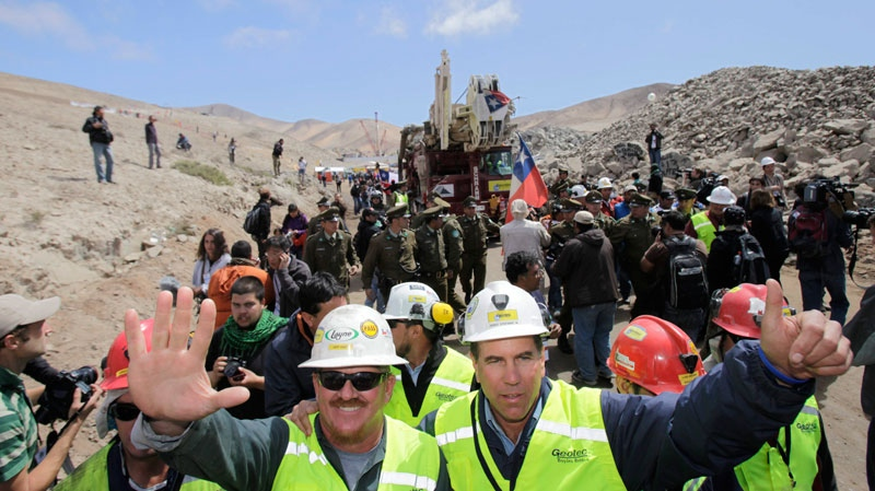 US drill operators Jeff Hart, left, and James Staffel wave as the T-130 drill that made the hole reaching the 33 trapped miners is transported away from the San Jose mine near Copiapo, Chile, Monday Oct. 11, 2010. (AP / Jorge Saenz)
