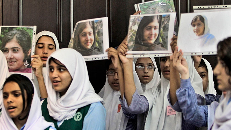 Pakistani students sing as they hold pictures of 14-year-old schoolgirl Malala Yousufzai, who was shot last Tuesday by the Taliban for speaking out in support of education for women, during a tribute at the Pakistani Embassy in Abu Dhabi, United Arab Emirates on Monday, Oct. 15, 2012. (AP / Kamran Jebreili)