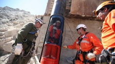 In this image released by the government of Chile, rescue workers prepare to release a colleague from a capsule after performing a dry run test for the eventual rescue of the 33 miners trapped at the San Jose mine, near Copiapo, Chile, Monday, Oct. 11, 2010. (AP / Government of Chile, Hugo Infante)