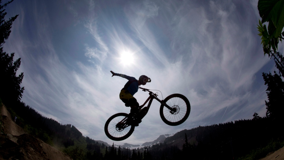 Mountain bike rider Paul Stevens is silhouetted as he rides the Whistler mountain bike park in Whistler, B.C. Monday, August 13, 2012. THE CANADIAN PRESS/Jonathan Hayward