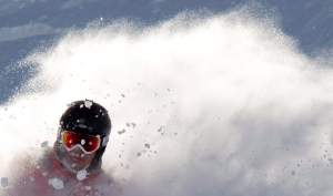 A sit skier plows though the snow during a powder day off of the Peak Chair on Whistler mountain in Whistler, B.C. Wednesday, April 4, 2012. THE CANADIAN PRESS/Jonathan Hayward