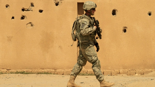 A U.S. Army soldier from A Co. 1st Battalion, 14th Infantry Regiment, 2nd Brigade, 25th Infantry Division, passes a bullet-riddled wall during a patrol in Hawija, north of Baghdad, Iraq on Tuesday, Aug. 31, 2010. (AP / Maya Alleruzzo)