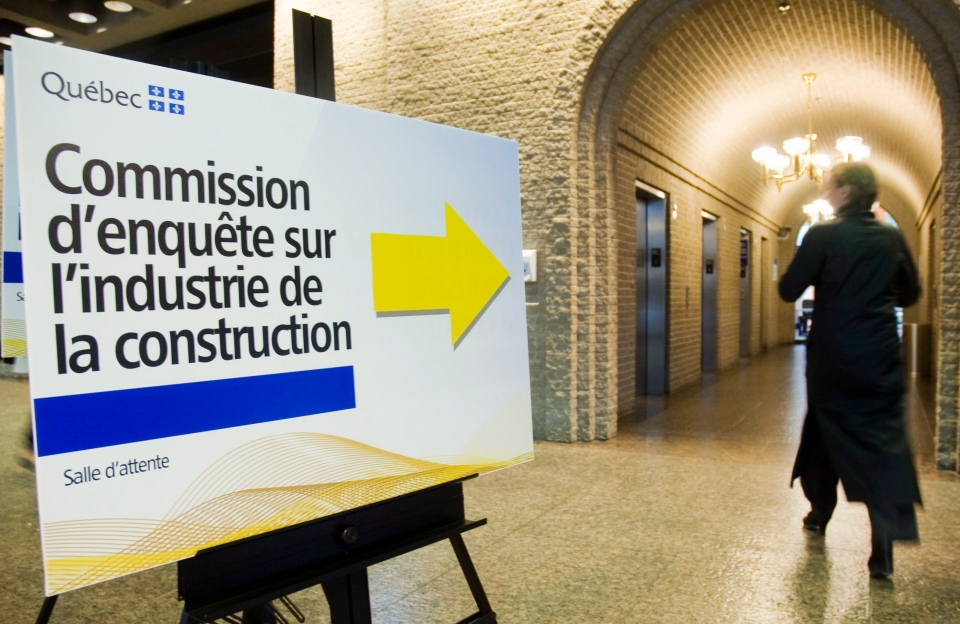 A woman walks by a sign pointing towards a security checkpoint in Montreal, Monday, June 4, 2012 at a Quebec inquiry looking into allegations of corruption in the province's construction industry. (Graham Hughes / The Canadian Press)