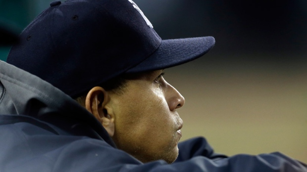 Alex Rodriguez watches from the dugout.